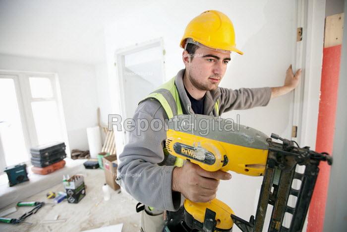 A carpenter working fitting a door frame, new housing near Taunton, Somerset. - Paul Box - 2012-03-22