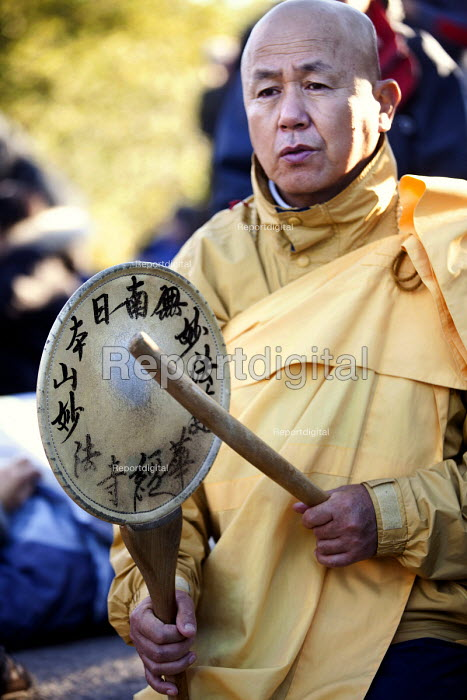 A Tibetan Monk banging a drum. Stop New Nuclear stage a die-in at the entrance to Hinkley Point . EDF Energy plans to build a new nuclear reactor at Hinkley point, Hinkley C power plant Somerset. - Paul Box - 2012-10-06