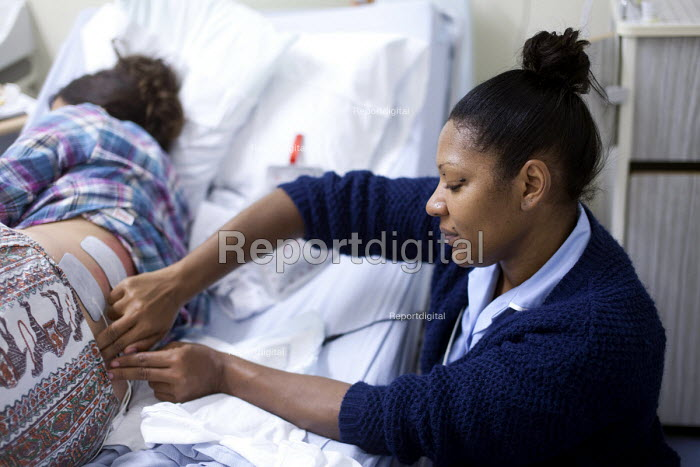 A student midwife massages a pregnant woman in labour who is an IVF patient who has obstetric cholestasis a rare complication of pregnancy. Which is a build-up of bile acids in the bloodstream and liver. Southmead hospital, Bristol. - Paul Box - 2012-09-23