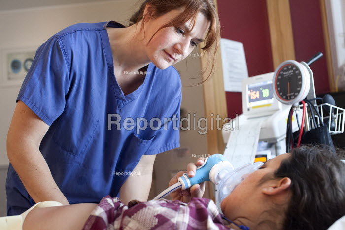 A midwife comforts a woman in labour who is an IVF patient who has obstetric cholestasis a rare complication of pregnancy. Which is a build-up of bile acids in the bloodstream and liver. Southmead hospital, Bristol. - Paul Box - 2012-09-24