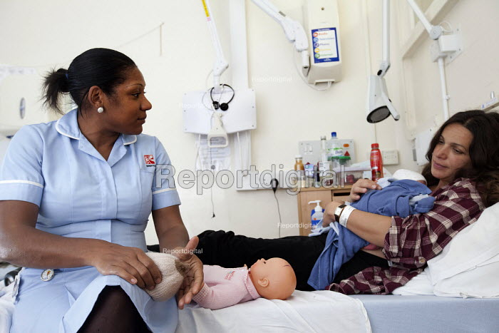 A student midwife explains to a new mother how to breast feed, hours after she gave birth. The mother is an IVF patient who has obstetric cholestasis a rare complication of pregnancy. Which is a build-up of bile acids in the bloodstream and liver. Southmead hospital, Bristol. - Paul Box - 2012-09-24