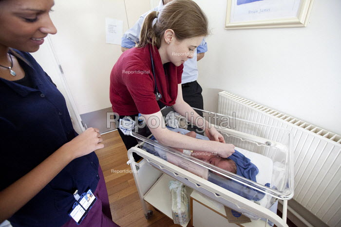 A doctor and medical students examines a new born baby boy hours after he was born. The mother is an IVF patient who has obstetric cholestasis a rare complication of pregnancy. Which is a build-up of bile acids in the bloodstream and liver. Southmead hospital, Bristol. - Paul Box - 2012-09-25