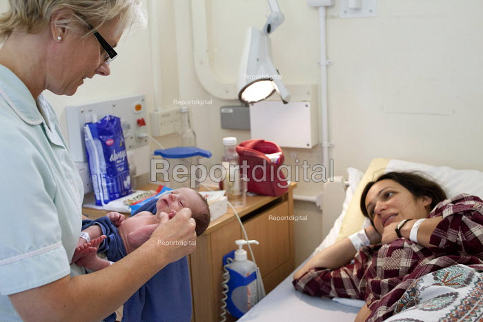A healthcare assistant examines a new born baby boy hours after he was born. The mother is an IVF patient who has obstetric cholestasis a rare complication of pregnancy. Which is a build-up of bile acids in the bloodstream and liver. Southmead hospital, Bristol. - Paul Box - 2012-09-25
