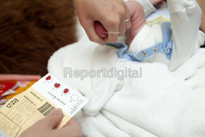 A midwife carries out a screening test on a new born boy at the mothers home. Bristol - Paul Box - 2012-10-05