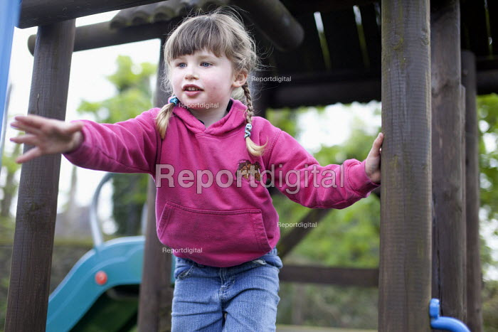 A 4 year old girl plays on her climbing frame, Wrexham, Wales - Paul Box - 2012-04-28