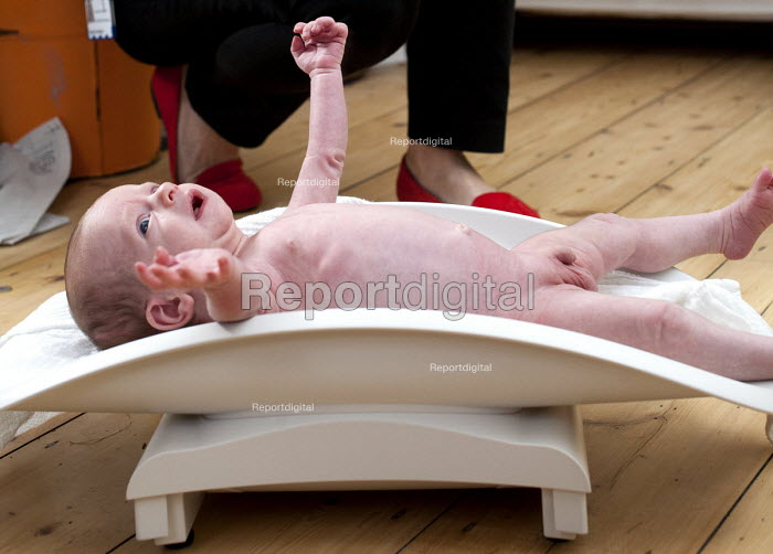 A 4 week old baby is weighed at home by the midwife, Bristol. - Paul Box - 2012-10-23