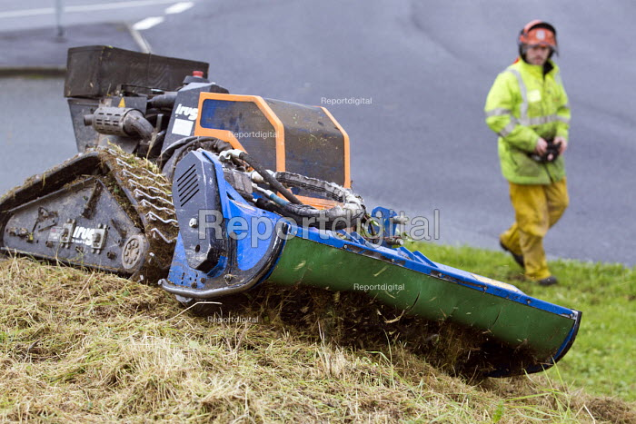 Deltrak Irus a remote control mower and ground clearance machine being used by council workers for clearing ground at the side of main roads. Wales. Used for maintaining brush and scrubland in normally inaccessible areas. - Paul Box - 2012-11-26