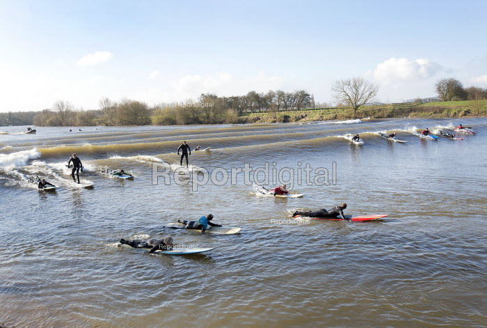 Surfers on The Severn bore tidal wave, on one of the largest tides of the year. Gloucestershire. - Paul Box - 2015-03-21