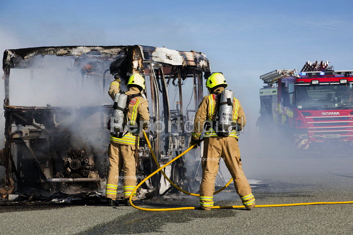 Firefighters extinguish a fire after The Pembrokeshire Coastal Cruiser tourist passenger bus burst into flames, Freshwater West, Wales - Paul Box - 2015-06-26
