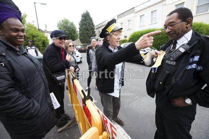 Sharing a joke with the police as residents protesting at new resident parking scheme, St Pauls, Bristol. A protestor dressed as a parking attendant issuing mock parking tickets. - Paul Box - 2015-06-17