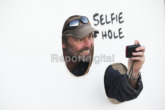 Dismaland a parody of Disneyland theme park by Banksy, Weston Super Mare. A visitor posing for a photograph through a selfie hole at the Bemusement Park. - Paul Box - 2015-08-27
