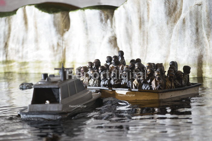 Dismaland a parody of Disneyland theme park by Banksy, Weston Super Mare. A drive a boat pond with boats full of refugees and the White Cliffs of Dover at the Bemusement Park. - Paul Box - 2015-08-27