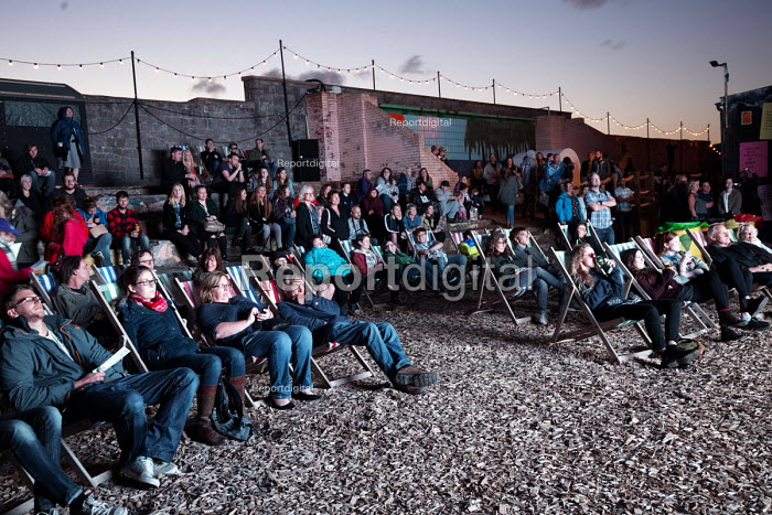 Dismaland a parody of Disneyland theme park by Banksy, Weston Super Mare. Audience watching a film at an outdoor cinema screening at the Bemusement Park. - Paul Box - 2015-08-27