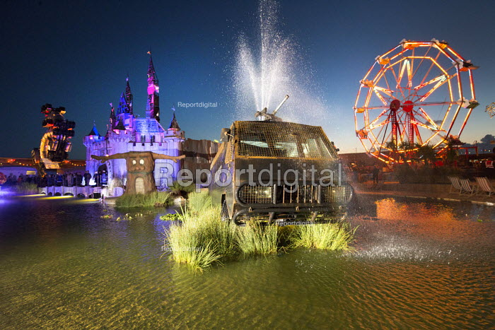 Dismaland a parody of Disneyland theme park by Banksy, Weston Super Mare. Giant Pin Wheel, Fairytale Cinderella castle, Big Rig Jig by Mike Ross Water Cannon Creek, Police armour plated riot control vehicle and slide at the Bemusement Park. - Paul Box - 2015-08-27