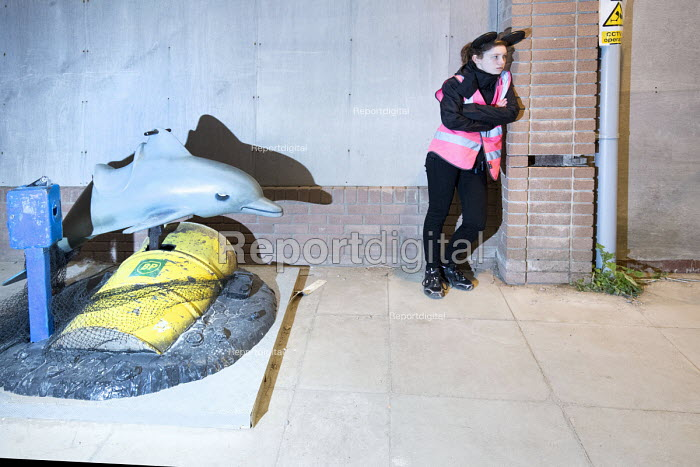 Dismaland a parody of Disneyland theme park by Banksy, Weston Super Mare. A Bemusement Park staffed by morose Dismaland guides who are uninterested in being helpful or remotely informative. Reconditioned dolphin ride with BP crude oil drum and a tuna net - Paul Box - 2015-08-27
