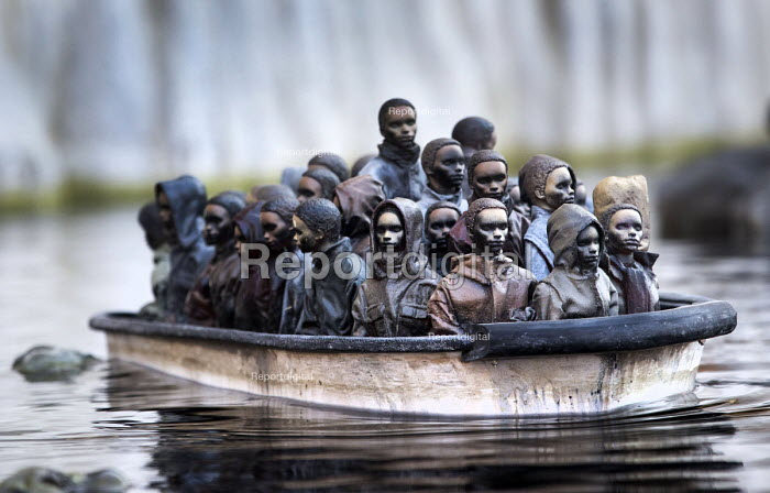 Dismaland a parody of Disneyland theme park by Banksy, Weston Super Mare. A drive a boat pond with boats full of refugees at the Bemusement Park. - Paul Box - 2015-09-07