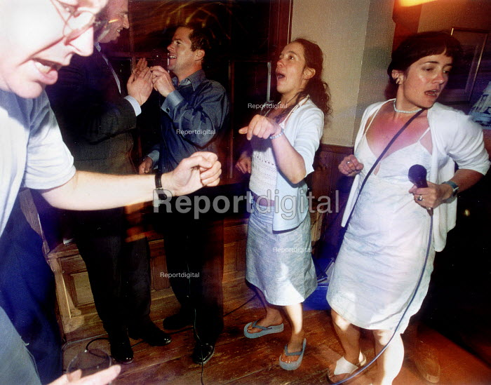 Party goers singing karaoke and dancing. - Paul Box - 2002-07-14