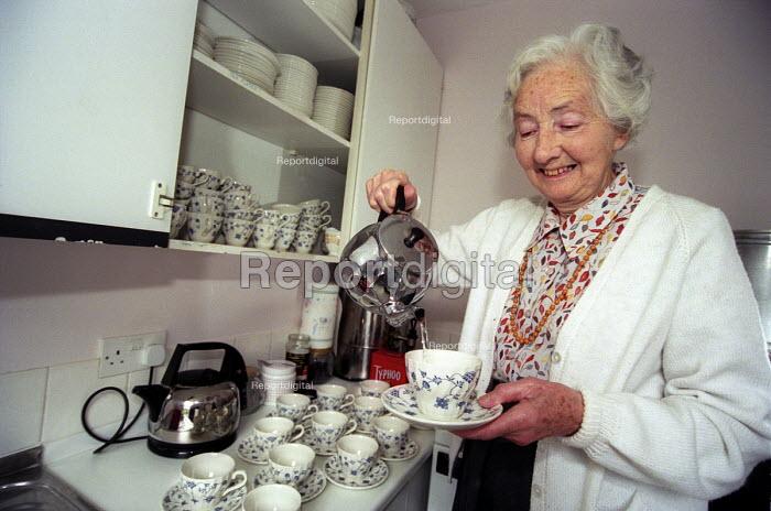 Happy elderly woman making tea in her kitchen at her retirement home, Bristol - Paul Box - 2003-12-01