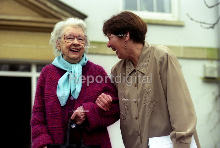 A happy elderly lady outside her retirement home, Bristol with a helper - Paul Box - 2003-12-01