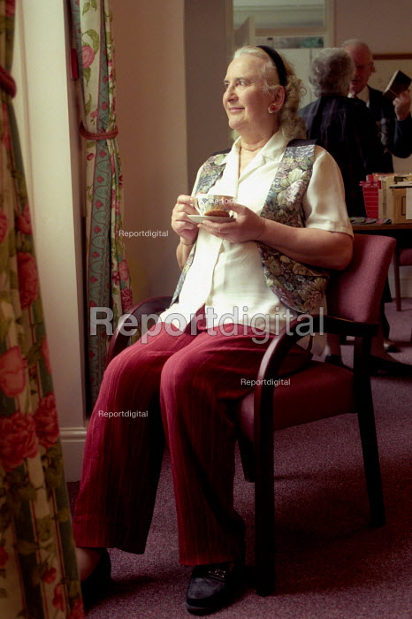 A happy elderly lady looks out the window of her retirement home, Bristol - Paul Box - 2003-12-01