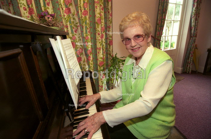 A happy elderly woman plays the piano at her retirement home, Bristol - Paul Box - 2003-12-01