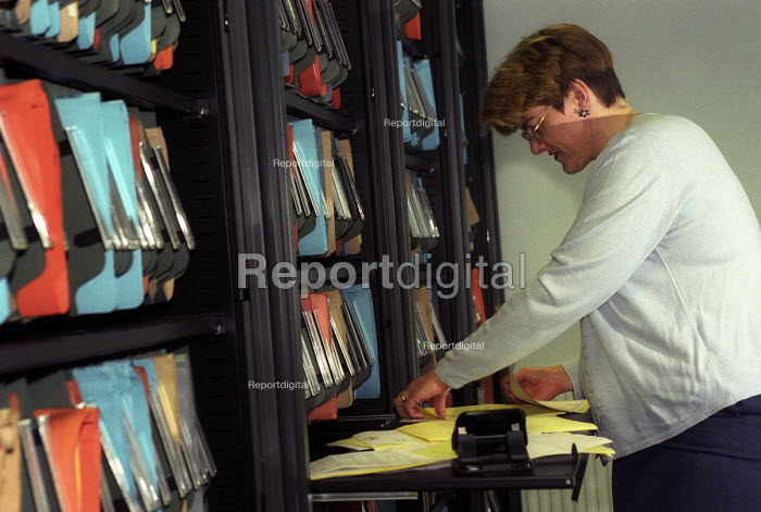 An office worker sorting through files. - Paul Box - 2003-12-07