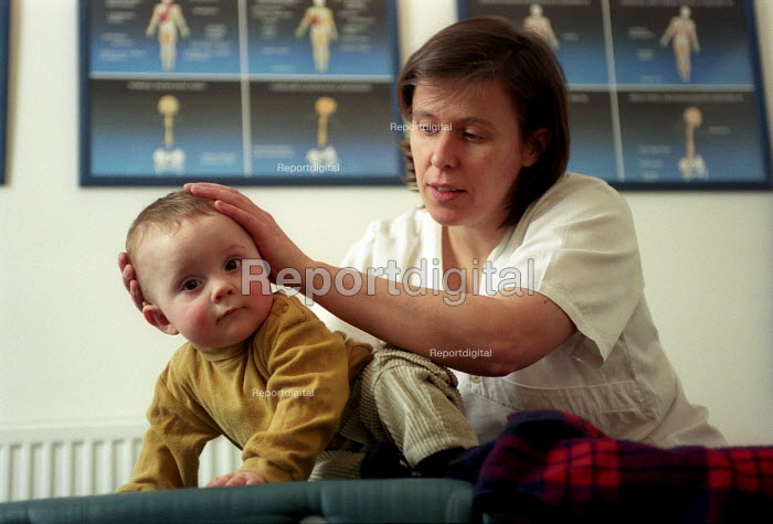 A young child visits a chiropractor for a head massage, Bristol - Paul Box - 2003-12-01