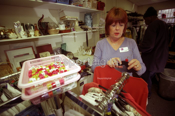 Charity shop , a volunteer prepares clothes for sale, Bristol - Paul Box - 2003-12-01