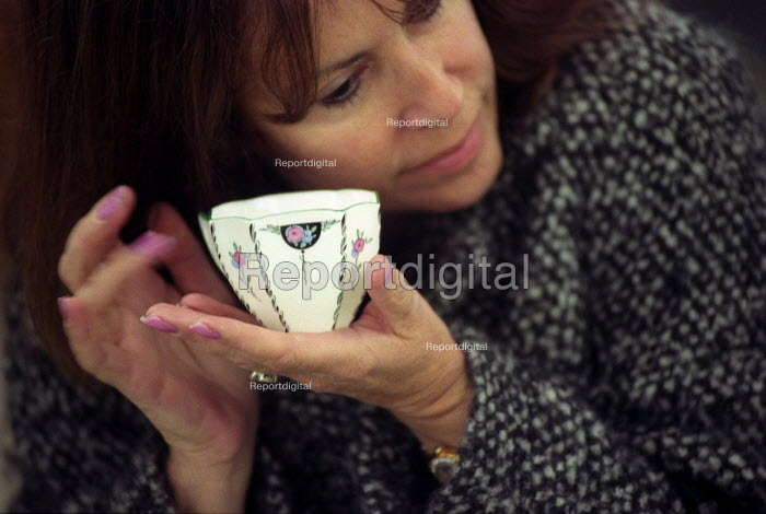 An Auction house Bath a lady checks the quality of a collectable tea cup - Paul Box - 2003-11-01