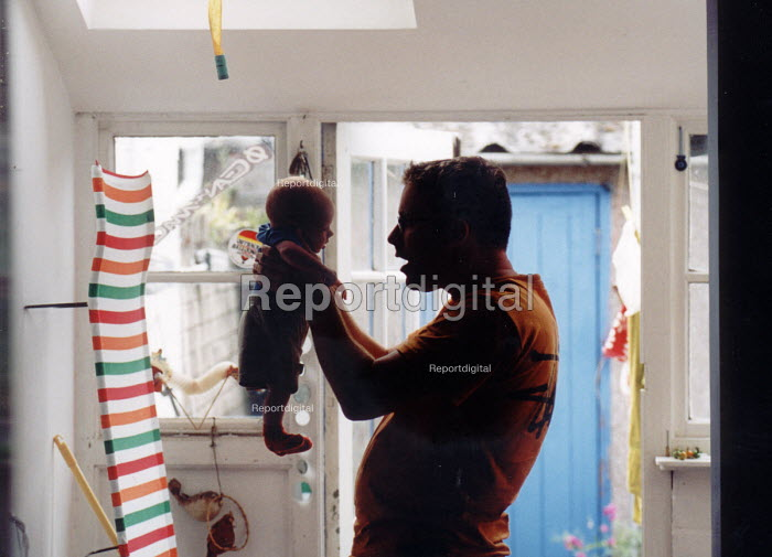 Baby and father at home. - Paul Box - 2003-01-18