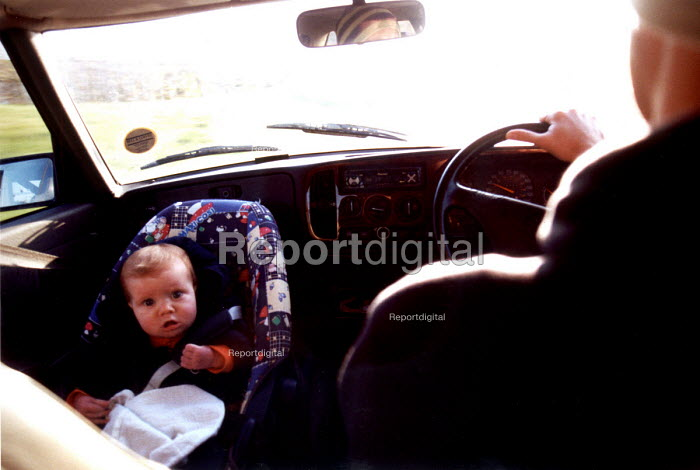 Baby strapped into a child safety car seat as mother drives the car. - Paul Box - 2003-01-18