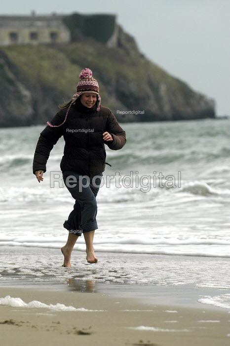 A woman runs down the beach , Tenby , Wales - Paul Box - 2004-01-20