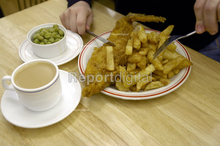 A woman eats fish and chips in a cafe in Tenby - Paul Box - 2004-01-20