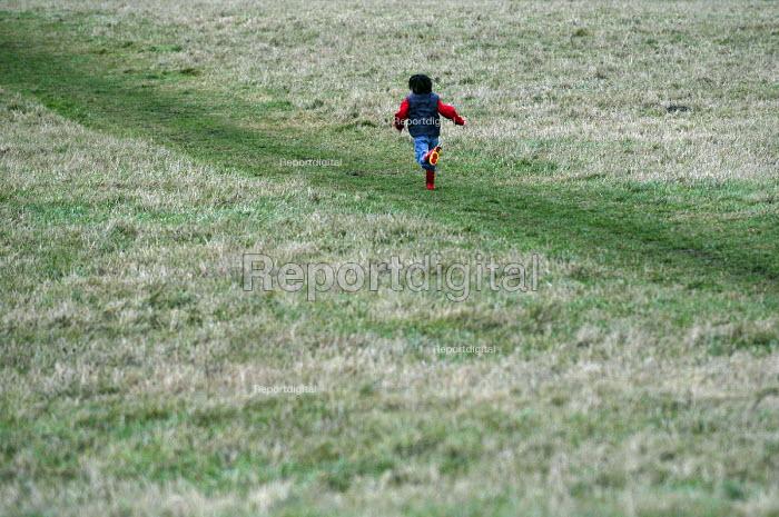 A young boy runs in a field - Paul Box - 2003-01-20