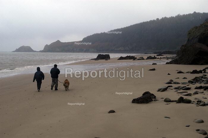 A couple walk their dog on a beach, Monkstone point, Pembrokeshire, Wales - Paul Box - 2004-01-11