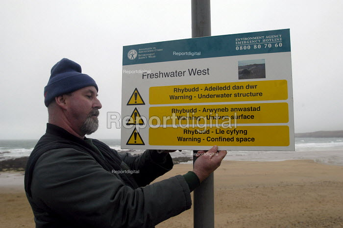 A council worker erects a sign warning of uneven surface on beach, Freshwater West , Wales. The sign is in Welsh and English. - Paul Box - 2004-01-01