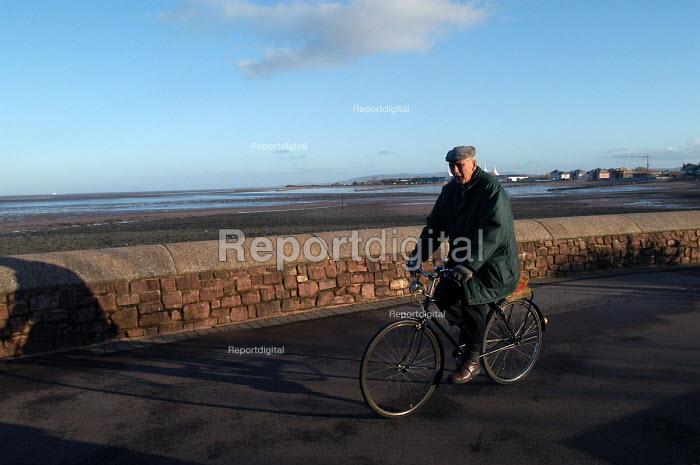 An elderly man cycles on the sea front, Minehead. - Paul Box - 2004-01-11