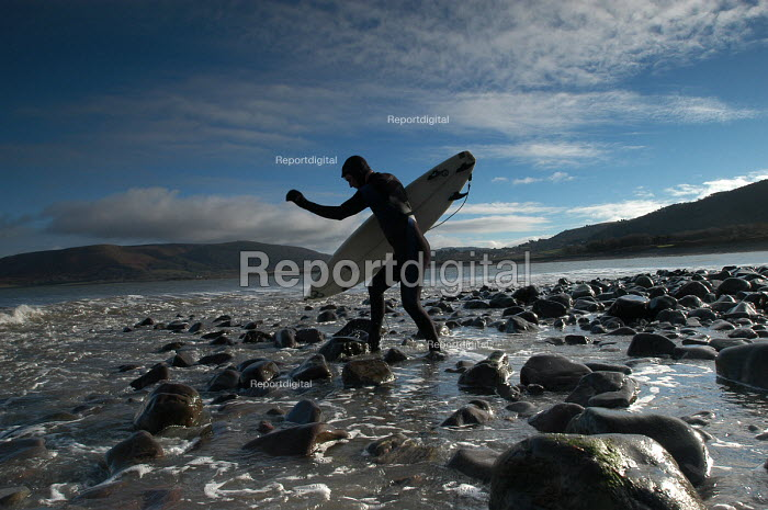 A surfer walks over rocks to go surfing - Paul Box - 2004-01-20