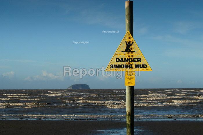 Danger sign warning of mud. Weston Super Mare beach . Steep holm island on horizon - Paul Box - 2004-01-10