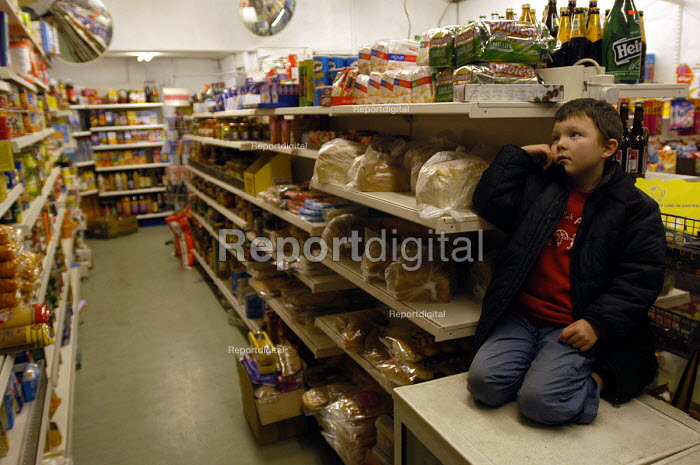 A child sits in corner shop whilst single mother works behind the counter. - Paul Box - 2004-01-20
