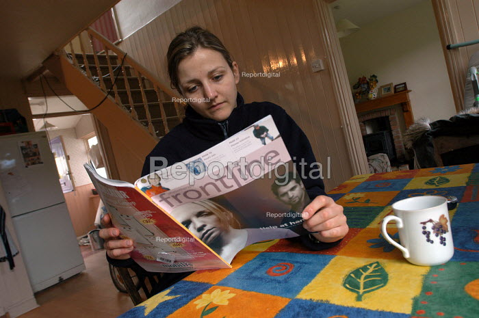 A physiotherapist relaxes at home reading the magasine, Front Line - Paul Box - 2003-11-01