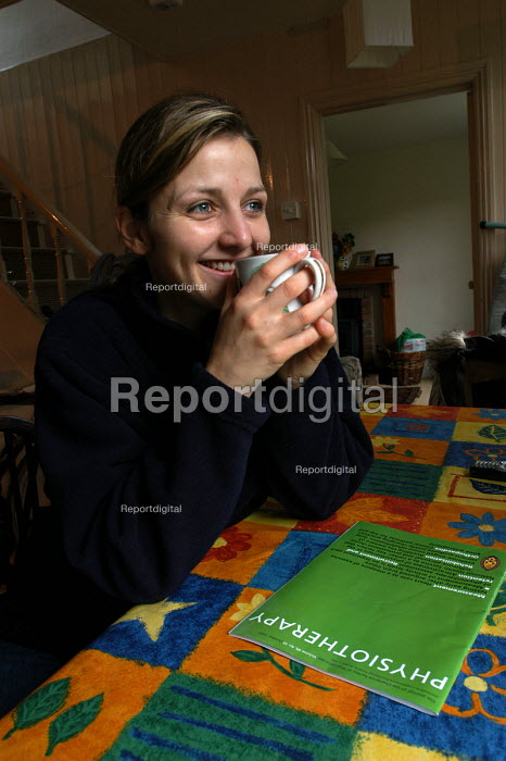 A physiotherapist relaxes at home reading the magazine Physiotherapy - Paul Box - 2003-11-01