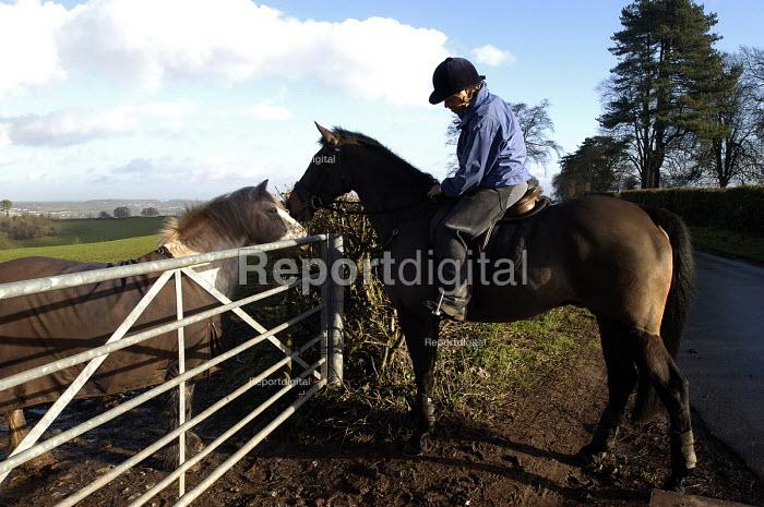 A horse rider walks on country road past warning sign near Bristol - Paul Box - 2004-01-10