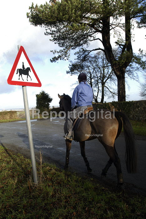 A horse rider walks on country road past warning sign near Bristol - Paul Box - 2004-01-10