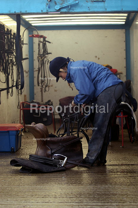 A female horse rider prepares her tack from tack room at a stables nr Bristol - Paul Box - 2004-01-01