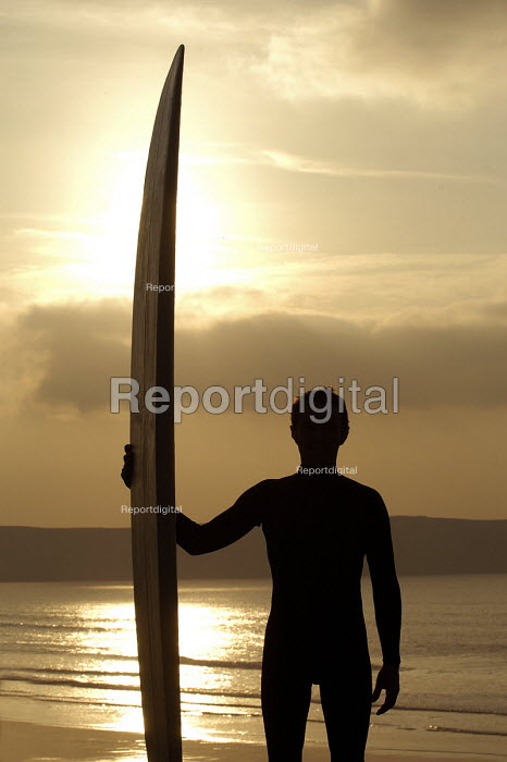 A surfer silhouetted against the setting sun , at Woolacombe Devon - Paul Box - 2004-01-20