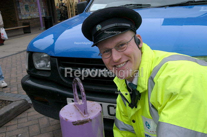 A security guard by a bollard preventing vehicle access to Yate shopping centre , south Gloucestershire - Paul Box - 2004-02-02