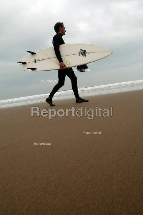 A surfer walks down the beach before going surfing - Paul Box - 2004-01-20
