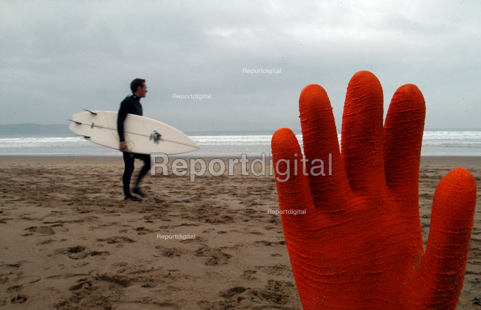 A surfer walks along the beach before going surfing with rubbish on beach. - Paul Box - 2004-01-20