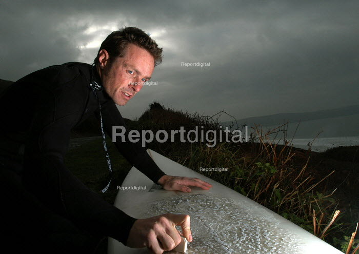 A surfer waxes his board on a winter day before going surfing at Woolacombe north Devon - Paul Box - 2004-01-20